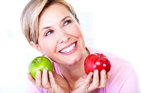 Smiling woman with dental implants in Torrington and apples