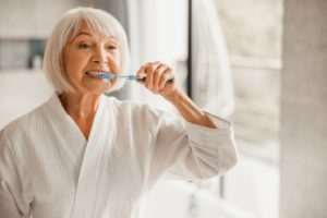 older woman at home brushing teeth during COVID-19