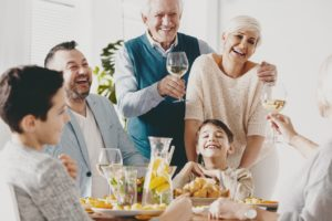 Grateful senior couple with dental implants enjoying dinner with family