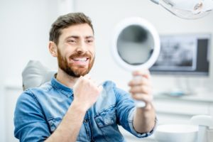 Man using mirror to examine his temporary veneers in Torrington
